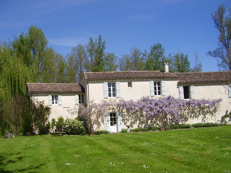 frontdoor Cottage. O glicínias na primavera-tempo, ao longo da frente da casa.