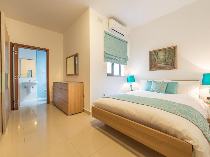 Quarto principal com cama de casal e casa de banho privada