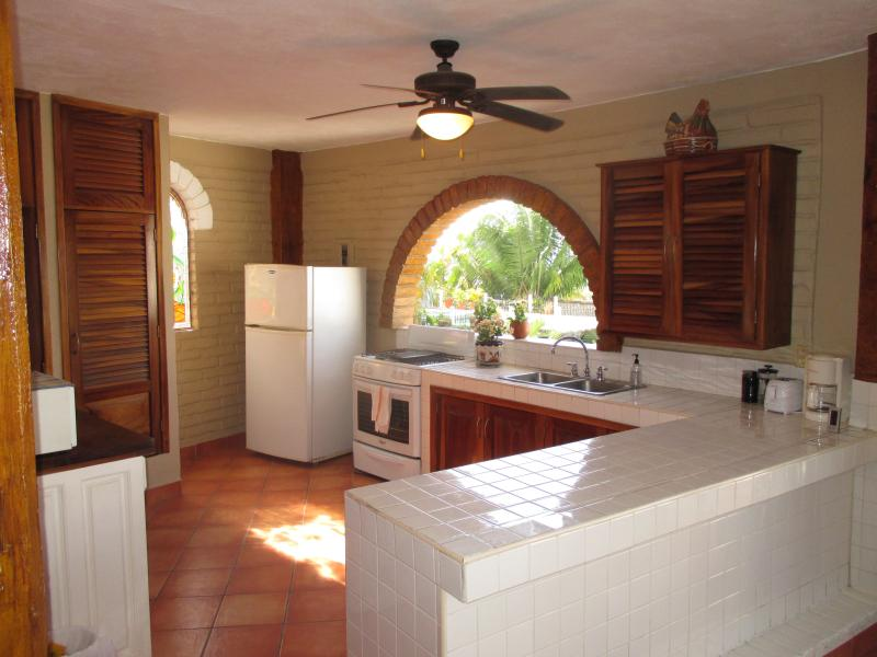 Fully equipped kitchen with open arch window overlooking Bandaras Bay