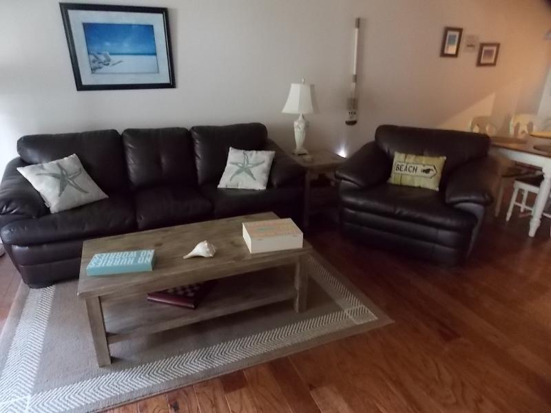 Cozy living room with leather sleeper sofa and leather chair, new wood floors throughout