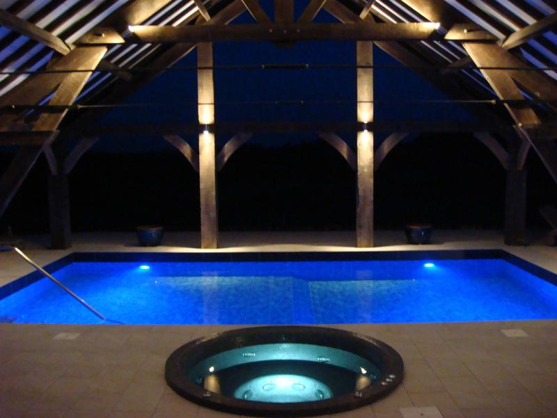 The Beautiful heated pool and hot tub lit up at night
