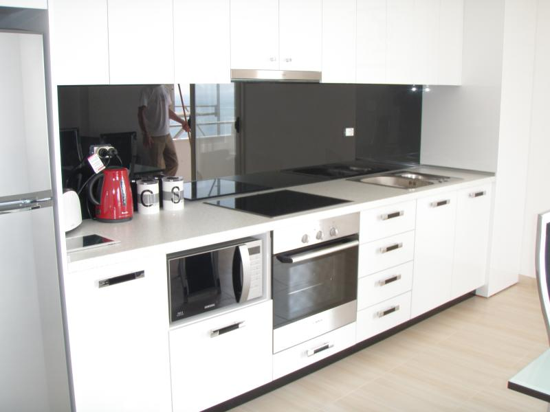 Modern kitchen with black glass splashback