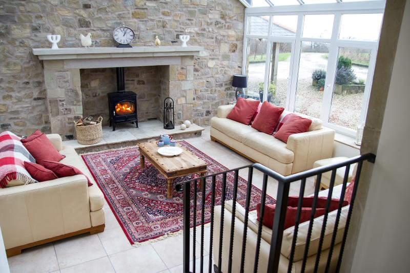 Magnificent conservatory with huge stone fireplace and wood burning stove, doors to garden areas