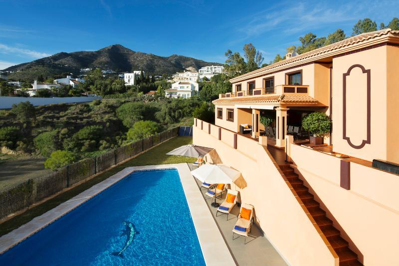 Traseira da casa, com enorme piscina e vistas deslumbrantes sobre as montanhas de Mijas.