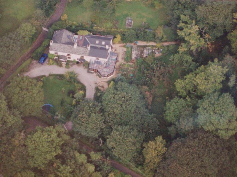 Een ariel van een deel van Badgers End Cottage in een privé bos met een aangrenzende boomgaard.