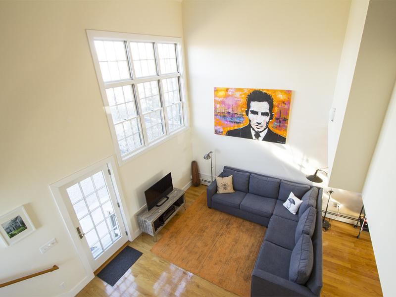 The living room features a soaring 19 ft ceiling and oversize north-sky-facing windows.