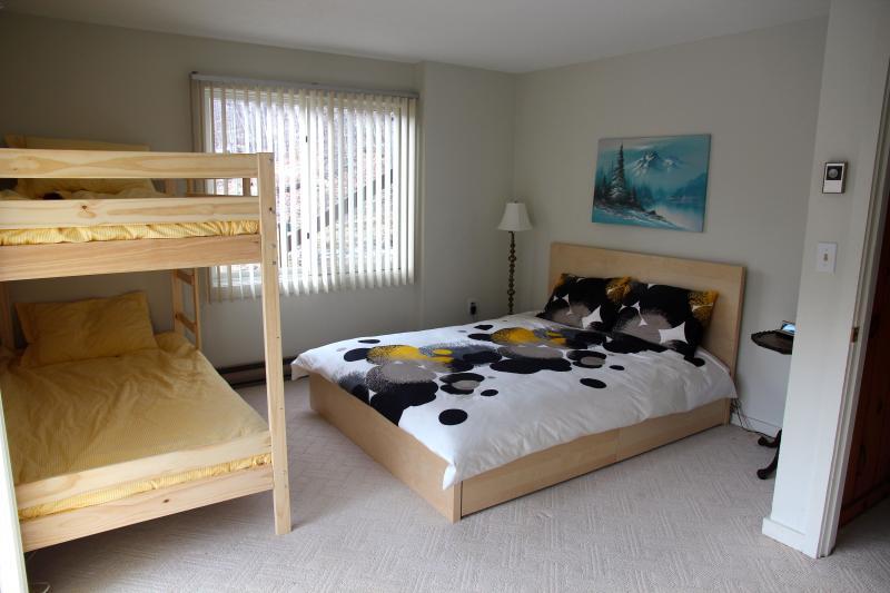 Quarto 1 com um beliche e uma cama queen-size.