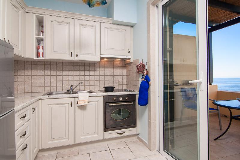 The fully equipped kitchen leads to a balcony, with a great sea view!
