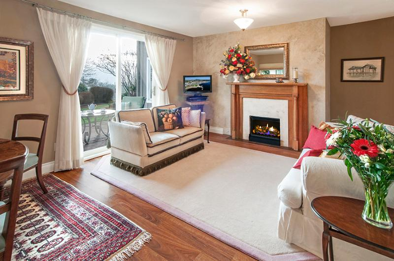 Living room with fireplace. Showing glass doors opening onto your generous, private patio with BBQ