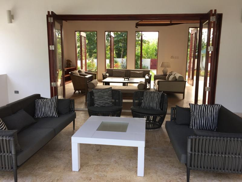 Veranda has comfortable seating, and views of the pool and living room.