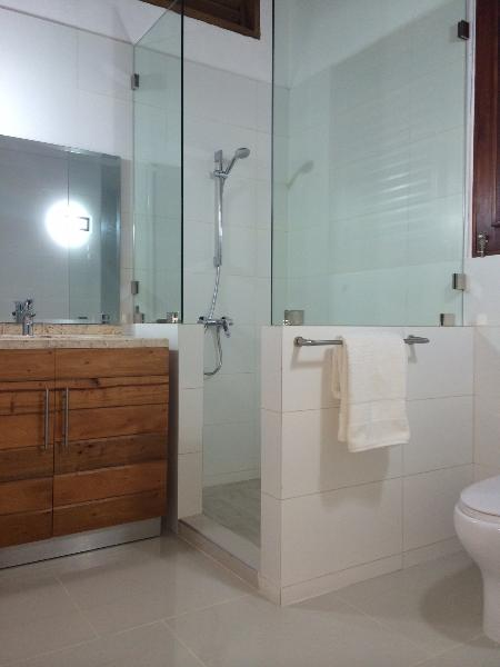 Guest bathroom has beautiful open glass shower and white tile