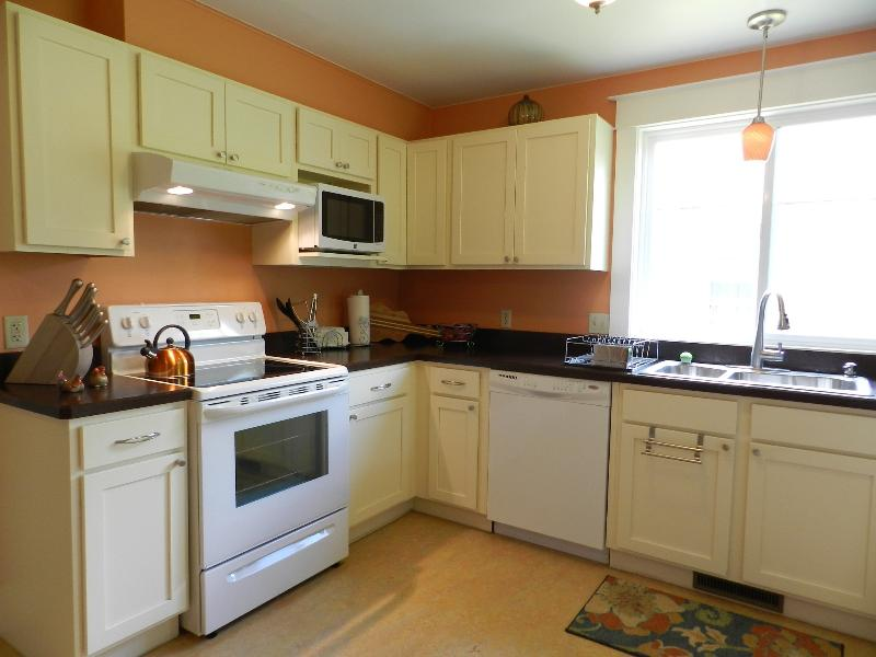 Sunny kitchen with stove, microwave, dishwasher with lots of dishes & cookware