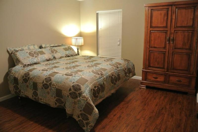 Bedroom with a queen bed located on main level just outside of kitchen.