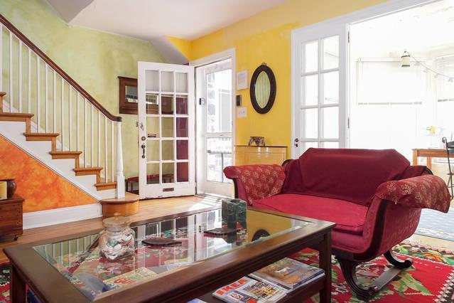 A entrada e sala de estar, escada e entrada para o Den