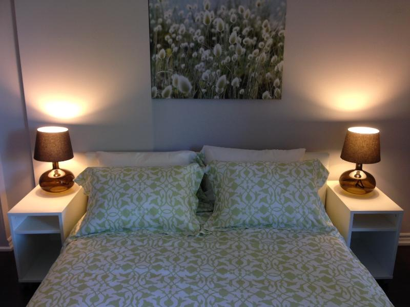 Fridfullt sovrum med hög kvalitet Queen-säng och fräscha sängkläder.
