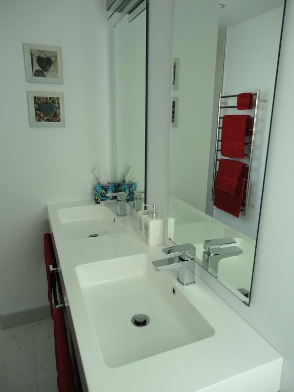 A well-appointed ensuite with double vanities, heated towel rail, mirrors and toasty warm tile floor