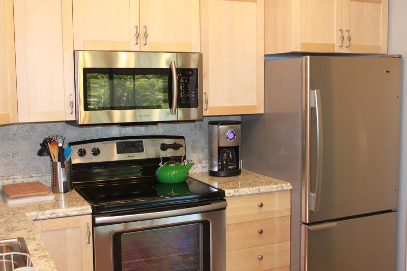 Mikrowelle, Kaffeemaschine, Herd und Kühlschrank.