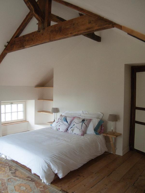 Bedroom with original wooden floors and beams.