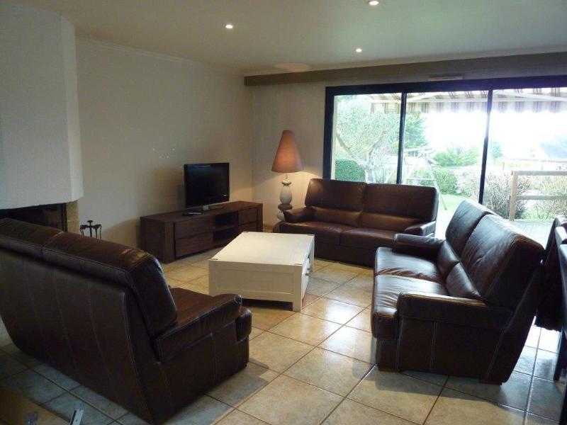 habitación con sofás, TV y chimenea.