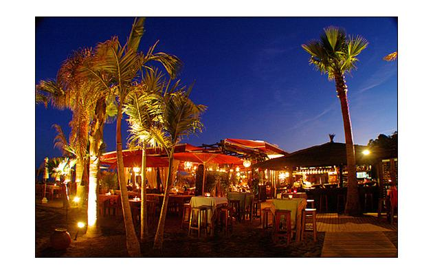 one of several beach bars by night