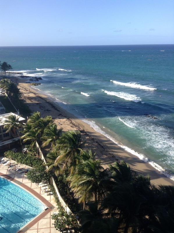 View of the ocean and swimming pool directly from the apartment window
