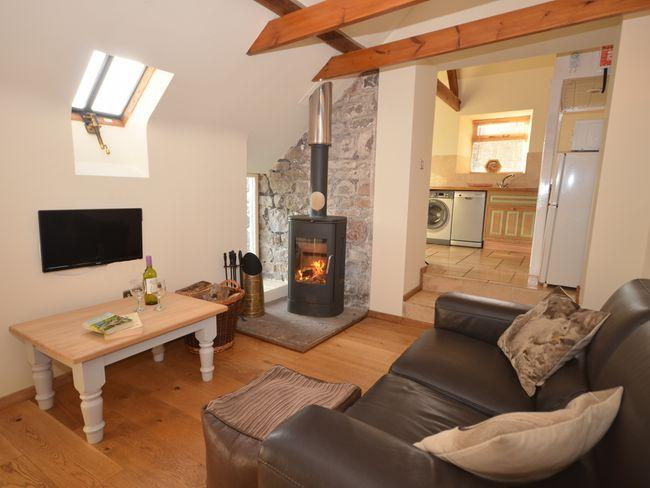 Lounge area with woodburner leading to the kitchen