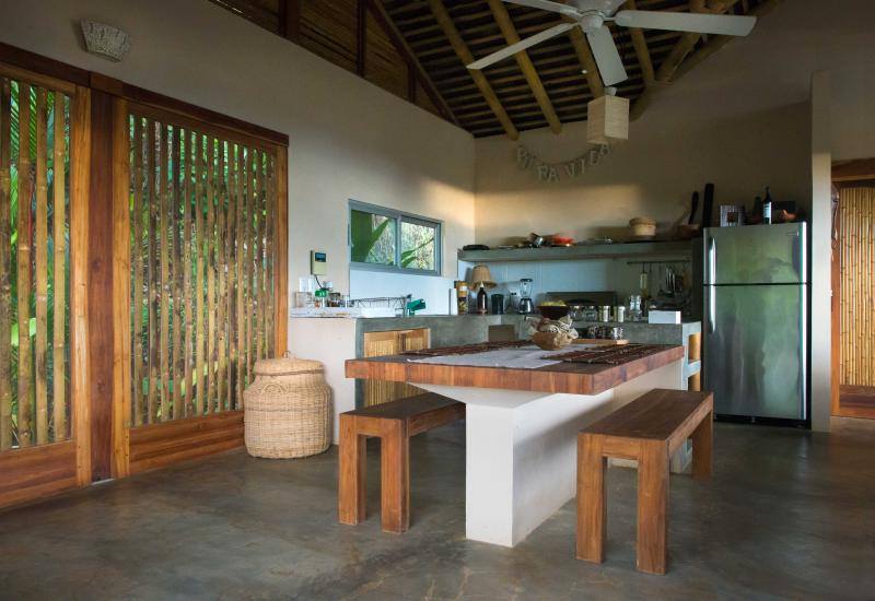 Fully equipped open-plan kitchen and dining area with new handmade teak benches for up to 6 people