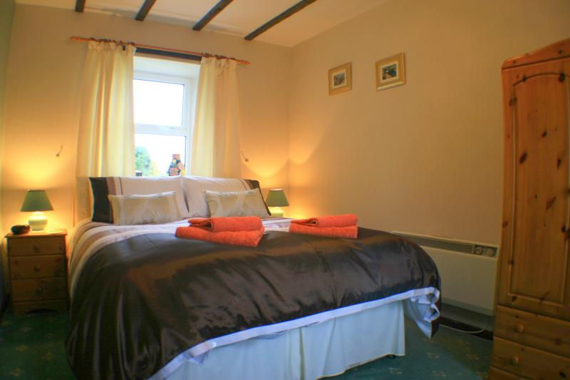 Old Stables Cottage Double Bedroom with wardrobe, digital radio alarm & leather armchair.