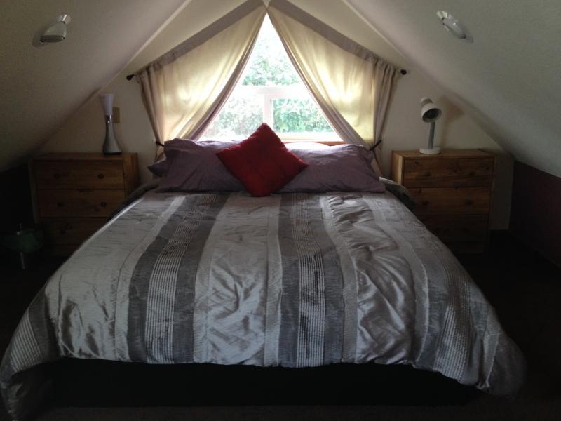 Loft Kamer met muur tot muur tapijt, kleine dressoirs en laden onder bed voor kleding.