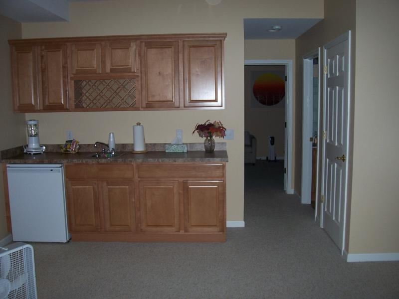 Lower level family room with wet bar and hallway leading to lower level bedroom.