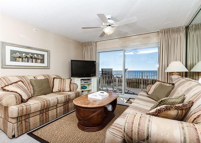 Beach front living room with plenty of seating and brand new flo