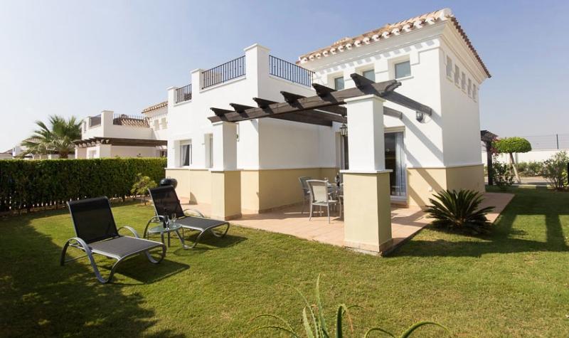 Vista posterior de villa con jardín soleado y tumbonas de calidad