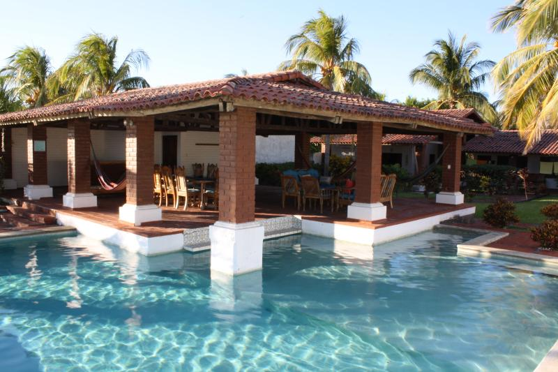 Pool with swim up bar, covered lanai and manicured grounds.