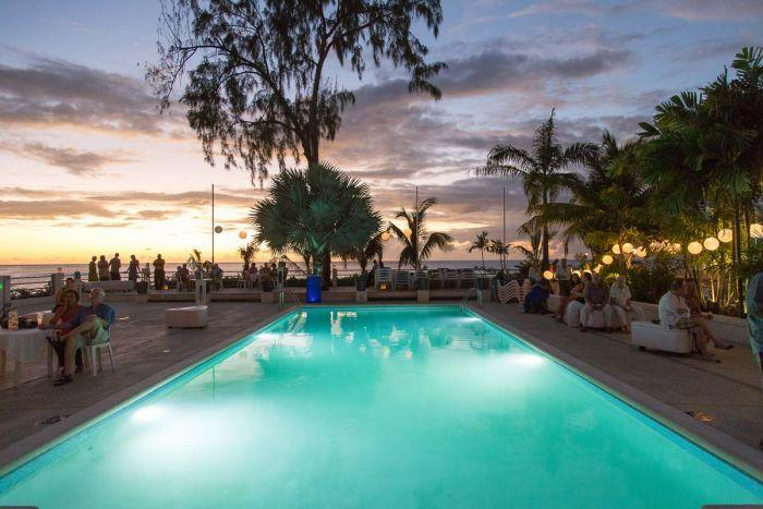 Beach club swimming pool at sunset (looking out at ocean).