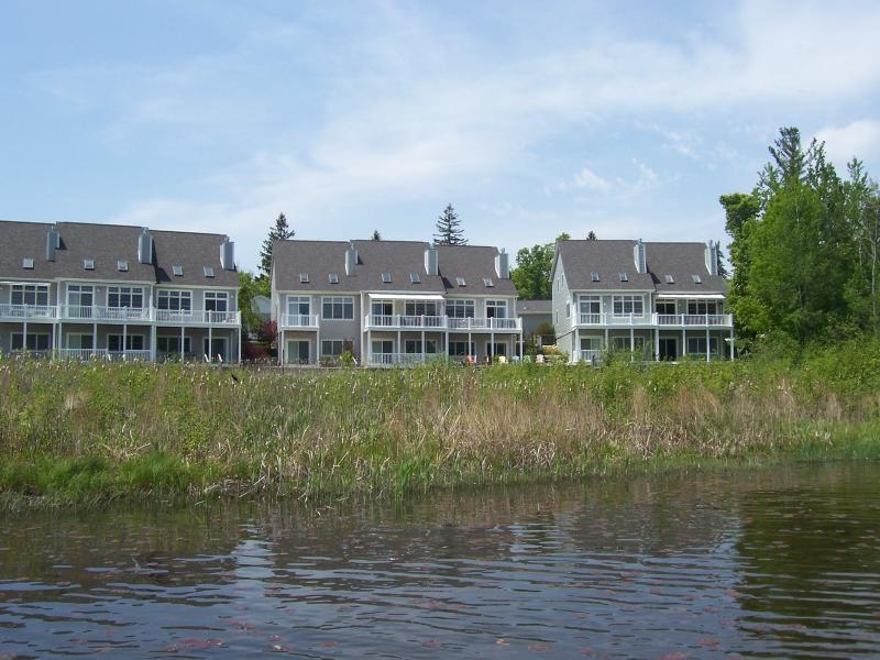 View of back of condo group from afloat in Hanley Lake.. Adirondack chairs lined up for relaxation.