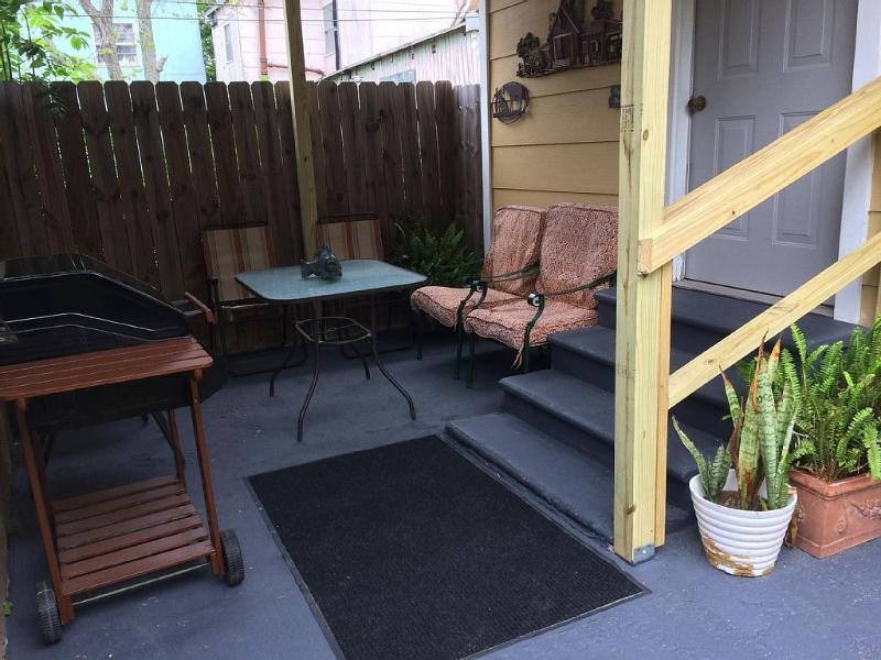Overdekte Patio: stoelen, tafel, en BBQ grill.