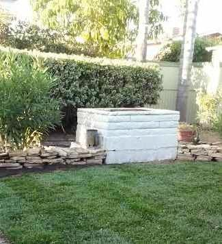 fenced back yard with fire pit