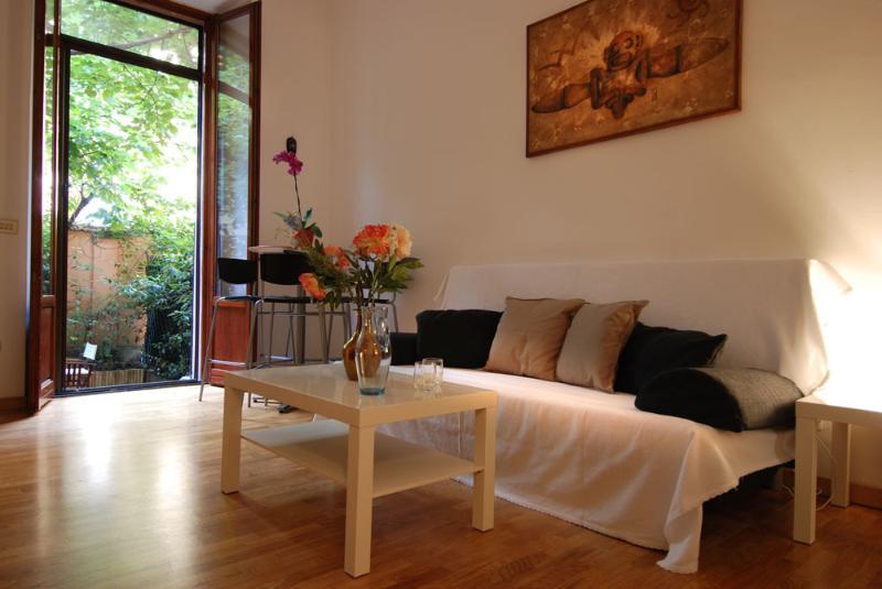 sala de estar con sofá cama y vistas al jardín