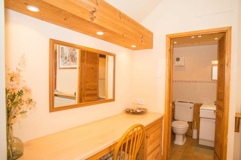 En-suite bathroom with toilet, basin and power shower.