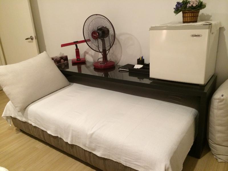 Sofa bed inside bedroom with mini fridge