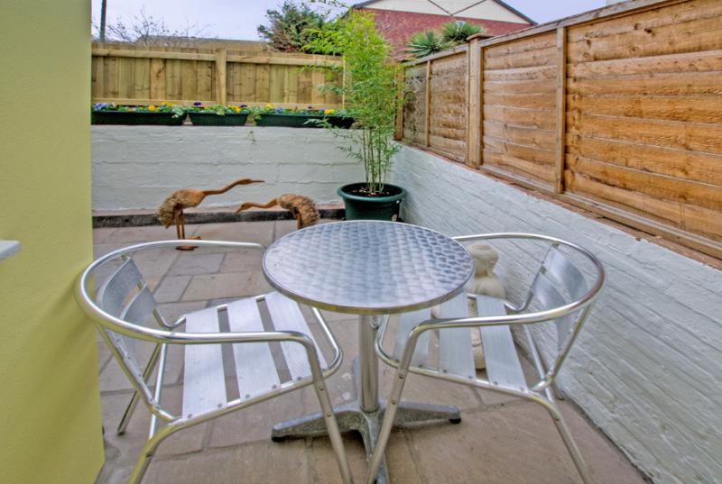 Enclosed patio with garden table and chairs.