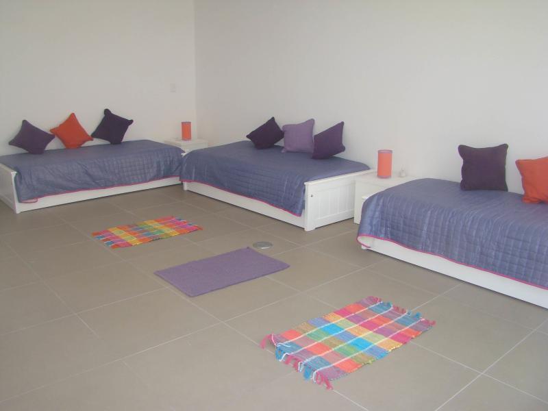 dormitorio con tres camas con carro cama para tres mas debajo, baño y vestidor