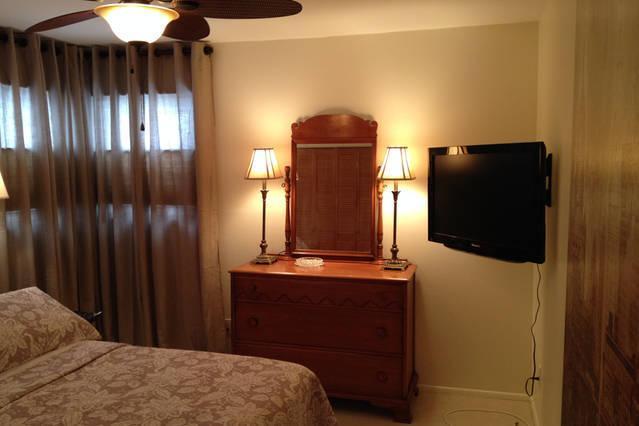 Hoofdslaapkamer met Queen size bed, flatscreen TV, DVD-speler over het hoofd zien zwembad.