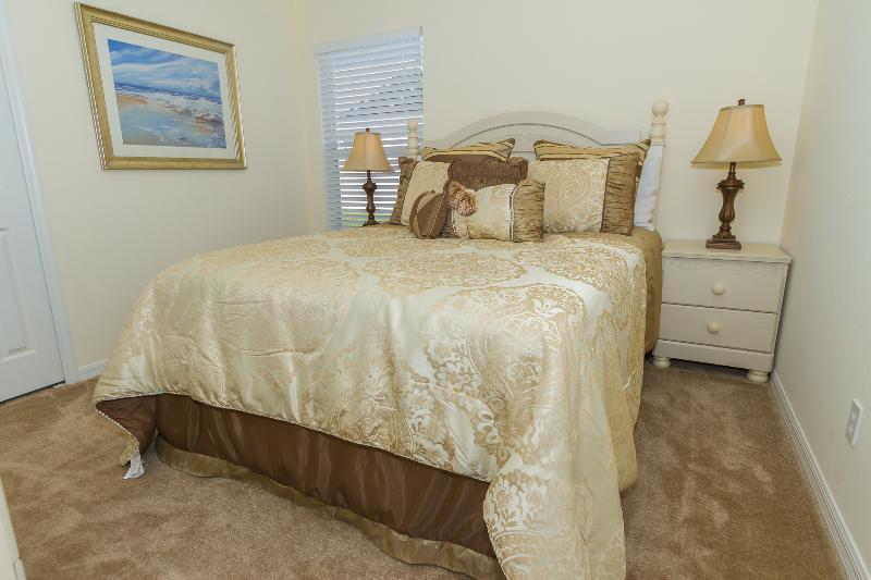 Quatro de quarto tem uma cama queen-size e televisão