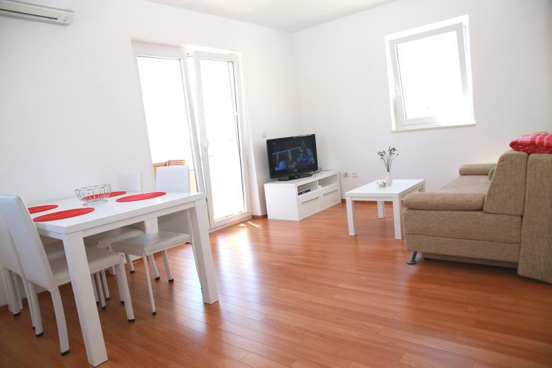 Sala de estar con TV de pantalla plana y aire acondicionado