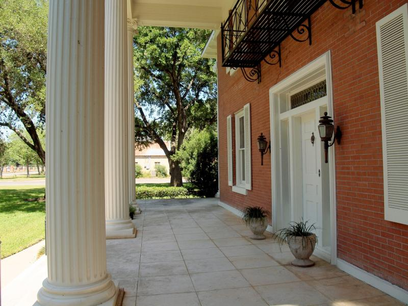 Front porch with white historical columns and balcony.