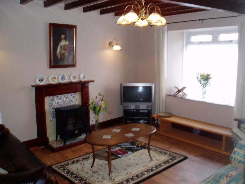 The living room, once the Post Office, has wooden beams, comfy sitting for 6 and TV