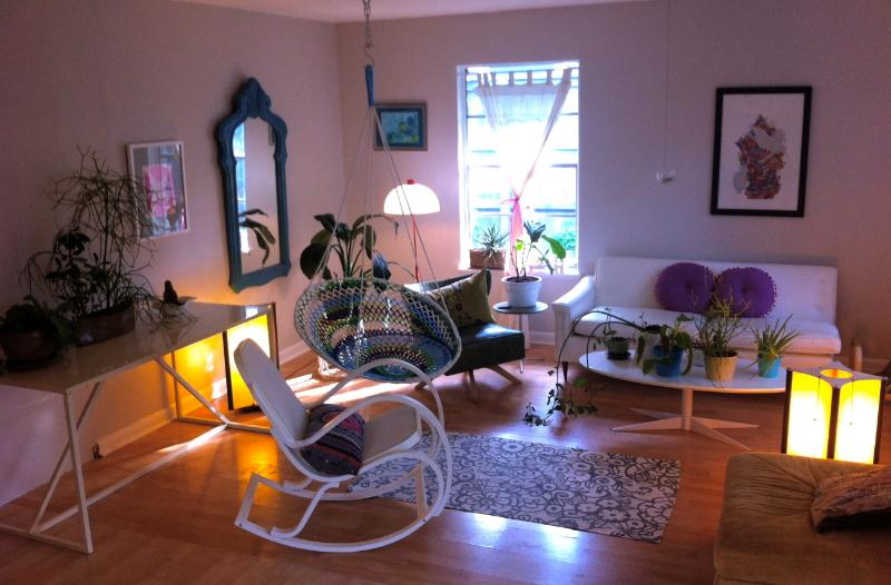 living room full of tropical plants, lovely lamps, and funky furnishings - including swing chair!