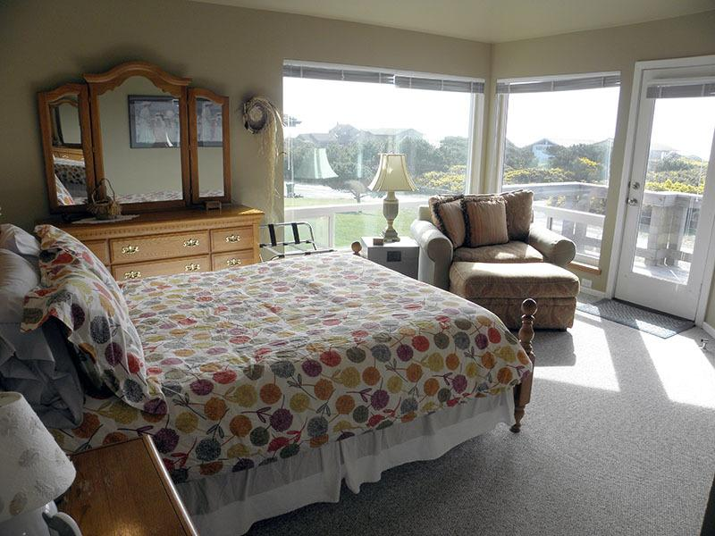 The master bedroom has a queen bed with a great ocean view and a fireplace.