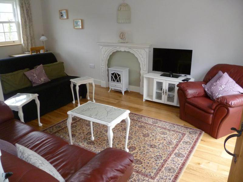 View of lounge showing leather settees and 32 inch Freesat HDTV